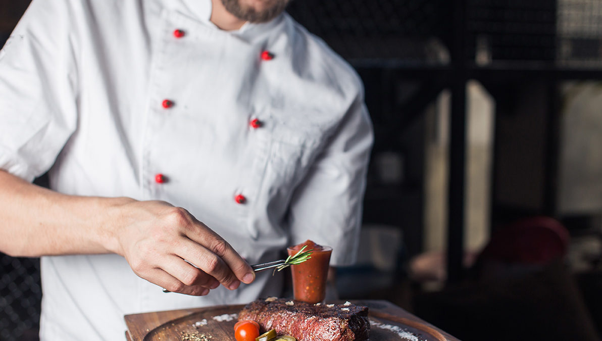 Restaurant chef avoiding temperature abuse when preparing a steak in the kitchen