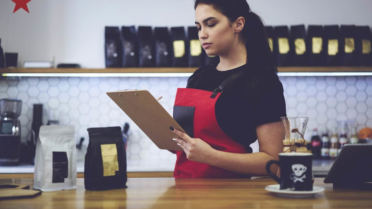 restaurant manager completing food safety checklist